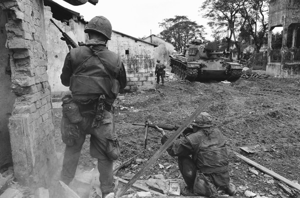 A U.S. service member, upper left, climbs from balcony to balcony while another, helmeted in center foreground, fires into a room during an effort to flush out Viet Cong fighters in a still-under construction hotel in Saigon, Vietnam, Jan. 31, 1968, near the South Vietnamese presidential palace. (AP Photo)