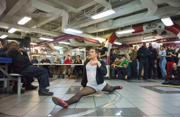 YN3 Joshua Kelley performs for sailors as 'Harpy Daniels' aboard the carrier Ronald Reagan in 2017. (MC3 Tyler D. John/Navy)