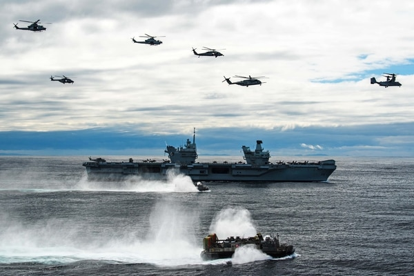 American aircraft fly in formation above the British Royal Navy aircraft carrier Queen Elizabeth as a landing craft, air cushion transits alongside on May 17, 2021, in the Atlantic Ocean. (Lt. Mark Nash/U.S. Navy)