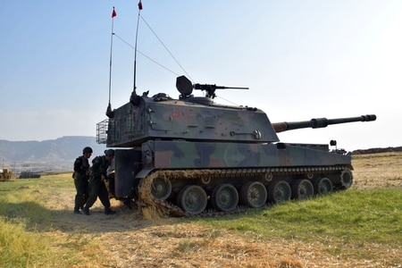 Turkish soldiers stand next to a tank during a military drill near the town of Silopi, Turkey, close to the Habur border gate between Turkey and Iraq, Wednesday, Sept. 20, 2017. Turkey's military says it has launched previously unannounced exercises near the border with Iraq, as the Iraqi Kurdish autonomous region prepares to hold a referendum on independence, scheduled for Sept. 25. (Turkish military/Pool photo via AP)
