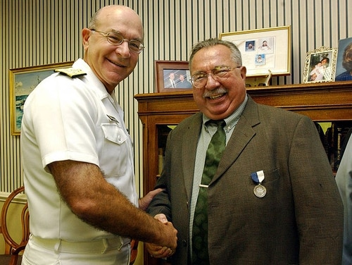 Adm. Vern Clark awards former Master Chief John Burlage with the Navy Superior Public Service Medal for his 18 years of outstanding reporting on issues affecting sailors. (Navy)