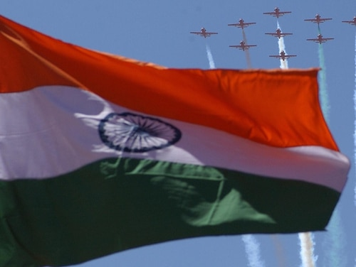 Kiran jets of the Indian Air Force's Suryakiran aerobatics team fly past the Indian national flag as they perform during the inaugural function of the Aero India 2005 air show at the Yelahanka Air Force Station on the outskirts of Bangalore on Feb. 9, 2005. (Indranil Mukherjee/AFP via Getty Images)