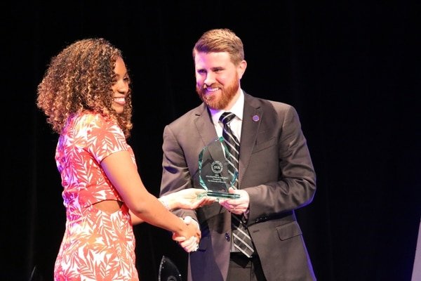 Student Veterans of America president and CEO Jared Lyon delivers the Chapter of the Year trophy to University of HoustonÕs SVA chapter president, Navy veteran Fontaine Wilson, during SVAÕs 2016 ÒNatConÓ National Conference in January.