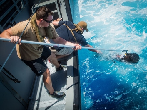Sailors assigned to Explosive Ordnance Disposal Mobile Unit 5 recover an underwater drone in the Pacific in May. (MC1 Torrey W. Lee/Navy)