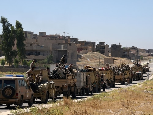 Iraqi government forces drive down a road leading to Tal Afar on June 9, 2017, during ongoing battles to retake the city from Islamic State group fighters. (Mohamed el-Shahed/AFP/Getty Images)