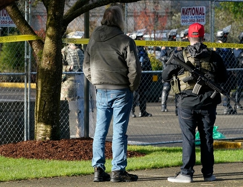An armed supporter of President Donald Trump looks in at a gathering of Washington State Patrol troopers behind a perimeter fence during a rally, Sunday, Jan. 10, 2021, at the Capitol in Olympia, Wash. (Ted S. Warren/AP)