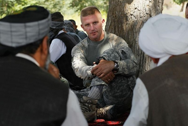 KHUSHI KHONA, HERAT PROVINCE, AFGHANISTAN - JUNE 22: Lt. Col. William Huff of the U.S. Army's 82nd Airborne Division, battalion commander of Task Force Professional, sits and talks with local Afghan leaders June 22, 2010 in the Khushi Khona area of Afghanistan, in Herat Province near the Turkmenistan border. Informal meetings with important local tribal and government officials (termed by the Army as KLEs, or Key Leader Engagements) are a crucial part of the counter-insurgency strategy that the American military has adopted in Afghanistan. The 82nd Airborne along with NATO Italian troops have been working for nearly a year in this historic area of Afghanistan, dotted with ancient villages just north of the cosmopolitan city of Herat. (Photo by Chris Hondros/Getty Images)