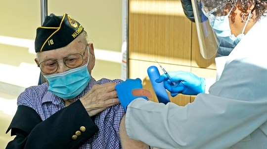 Army veteran Gene Moy, 103, of Seattle, receives the second shot of the Pfizer COVID-19 vaccination from Levone Walton (right) a nurse at the VA Puget Sound Health Care System campus in Seattle on Feb. 23, 2021. (Ted S. Warren/AP)