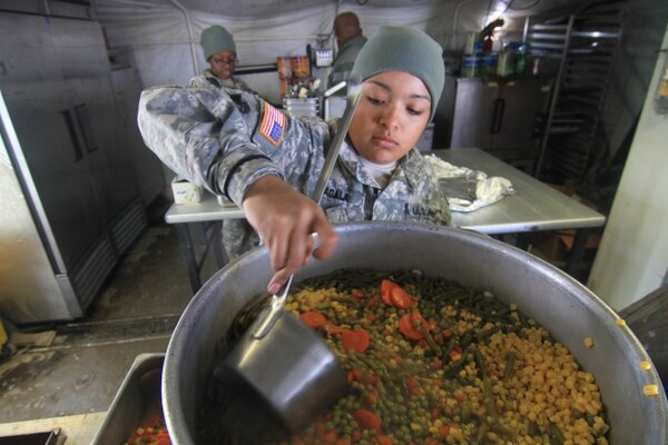 Spc. Alva Sagala, food service specialist, Forward Support Company H, 2nd Battalion, 23rd Infantry Regiment, 1st Stryker Brigade Combat Team, 4th Infantry Division, lades mixed vegetables into food storage containers as part of the evening meal sent to Soldiers, training on Fort Carson Feb. 23, 2015. (U.S. Army photo by Staff Sgt. Nancy Lugo, 1st SBCT PAO, 4th Infantry Division)