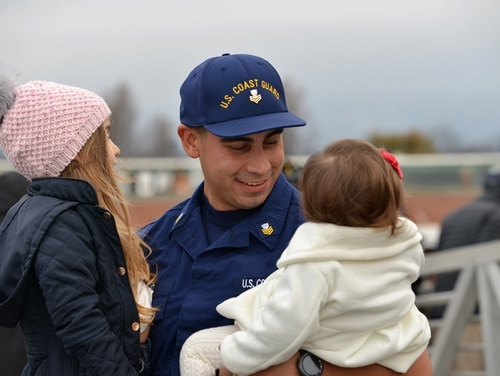 A crewmember from the Coast Guard Cutter Munro embraces his children after returning to California from a deployment at sea on Dec. 24, 2018. Coast Guard members will miss their second consecutive paycheck this month if the government shutdown continues to the end of the week. (Petty Officer 1st Class Matthew S. Masaschi/Coast Guard)