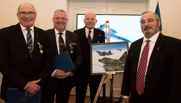 From left to right, Col. Lars-Erik Blad, Maj. Roger Moller, Maj. Krister Sjober, and retired U.S. Air Force Lt. Col. Tom Veltri stand beside the official photo which depicts the event that earned the Swedish pilots their U.S. Air Medals in Stockholm, Sweden. (Senior Airman Kelly O'Connor/Air Force)
