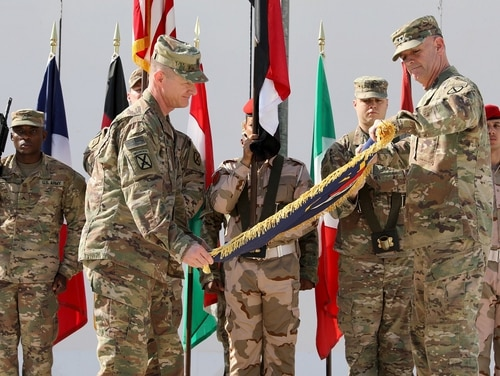 Maj. Gen. Walter Piatt, right, commander of Combined Joint Forces Land Component Command, and his senior enlisted adviser, Command Sgt. Maj. Samuel Roark, left, roll up the CJFLCC flag during a deactivation ceremony in Baghdad, Iraq, April 30. (Master Sgt. Horace Murray/Army)