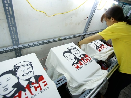 A worker removes t-shirts printed with portraits of President Donald Trump and North Korean leader Kim Jong Un at a shop in Hanoi, Vietnam, on Feb. 21, 2019. The two men are scheduled to hold another round of peace talks on February 27 and 28. (Hau Dinh/AP)