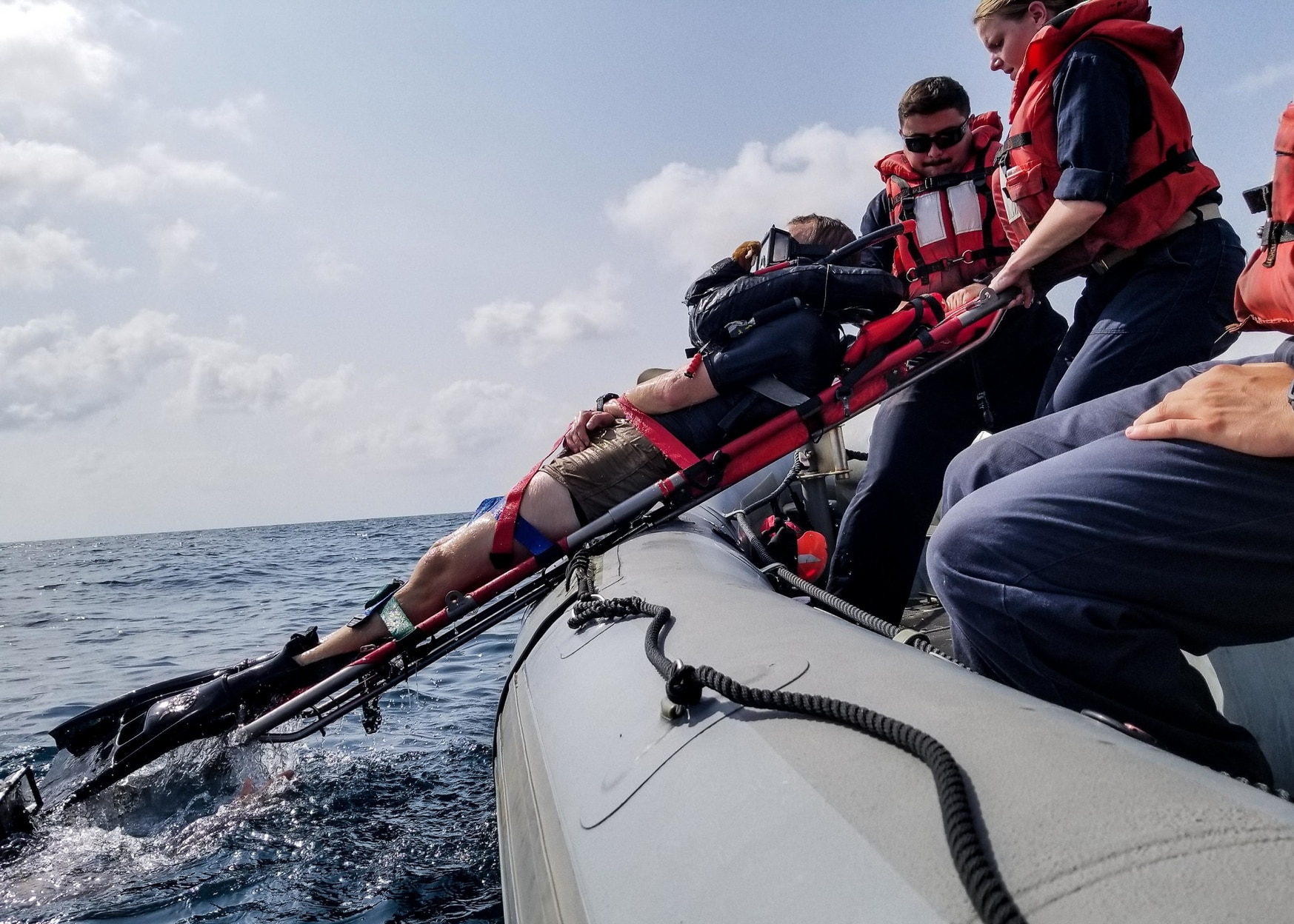 Ensign Samantha Rados, right, and Machinist's Mate 2nd Class Samuel Green, center, assigned to the warship Jason Dunham, pull Quartermaster 2nd Class Christopher McGann, a search and rescue swimmer out of the water on a litter into a rigid-hull inflatable boat during training during the ship's 2018 deployment. A few months before, their shipmate, Ensign Sarah Mitchell, died after falling from a RHIB and getting struck by the propeller. (Navy)