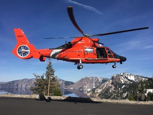 An MH-65 Dolphin helicopter lands at a parking area to transfer an injured man to AirLink Critical Care Transport on June 10, 2019, at Crater Lake National Park in Oregon. (Petty Officer 1st Class Levi Read/Coast Guard)