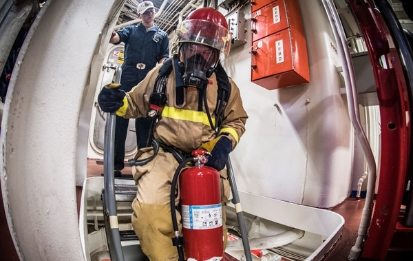 Turbine System Technician (Mechanical) Fireman Jacob Barczyk carries a fire extinguisher down a ladder well during a Dec. 17 general quarters drill on board the guided-missile destroyer Jason Dunham. (Mass Communication Specialist 2nd Class Jonathan Clay/Navy)