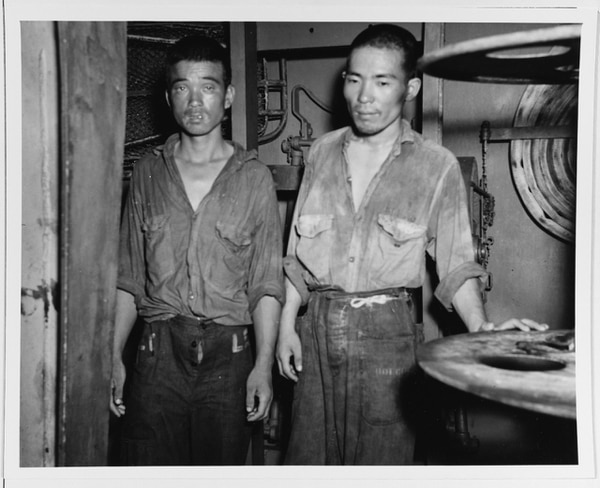 Two survivors of the sunken Japanese light cruiser Jintsu on board the destroyer Nicholas after the Battle of Kolombangara, 13 July 1943. They are dressed in well-worn U.S. Navy enlisted working uniforms. (National Archives)
