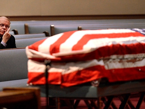 In this Jan. 10, 2019, photo, Rex Beach watches the flag-draped casket of his father, William Beach, from a pew at Canton Nazarene in Canton, Ohio. After an eight-year odyssey, Rex Beach found and then had to let go of a father he never knew. (Ray Stewart/The Canton Repository via AP)