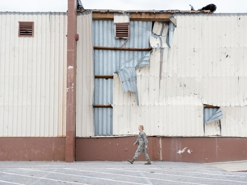An Airman walks past the 325th Logistics Readiness Squadron materiel management flight warehouse at Tyndall Air Force Base, Florida, March 13, 2019. Airmen from various Air Force installations have come to Tyndall in support of post Hurricane Michael recovery efforts. (Senior Airman Javier Alvarez/U.S. Air Force)