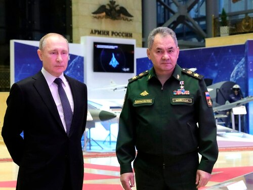 Russian President Vladimir Putin, left, and Defense Minister Sergei Shoigu speaks to journalists after attending an annual meeting with top military officials in the National Defense Control Center in Moscow on Dec. 24, 2019. (Mikhail Klimentyev/Sputnik, Kremlin Pool Photo via AP)