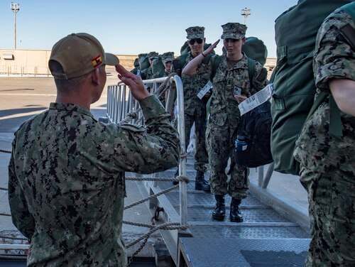 Sailors salute while boarding the USS Carney (DDG 64) in Naval Station Rota, Spain, on June 2, 2019. House lawmakers unveiled plans for a 3.1 percent pay raise and a host of other personnel changes in their draft defense authorization bill language released Monday. (Mass Communication Specialist 1st Class Fred Gray IV/Navy)