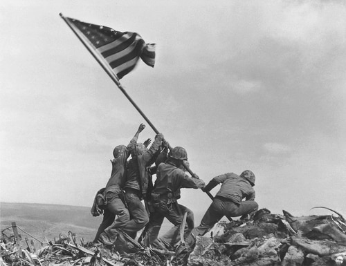 FILE - In this Feb 23, 1945 file photo, U.S. Marines of the 28th Regiment, 5th Division, raise the American flag atop Mt. Suribachi, Iwo Jima, Japan. The Marine Corps said Monday, May 2, 2016, that it has begun investigating whether it mistakenly identified one of the men shown raising the U.S. flag at Iwo Jima in one of the iconic images of World War II after two amateur history buffs began raising questions about the picture. The Marines announced its inquiry more than a year after Eric Krelle, a toy designer from Omaha, Neb., and Stephen Foley, who works at a building supply company in Wexford, Ireland, questioned the identity of one man. (AP Photo/Joe Rosenthal, File) ORG XMIT: CER101