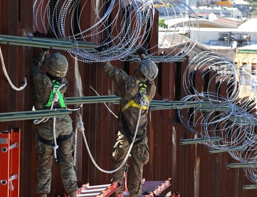 Soldiers from the 87th Sapper Company, 20th Engineer Battalion, 36th Engineer Brigade wire along the top of the border fence at the DeConcini Port of Entry in Nogales, Ariz. (Sgt. Kyle Larsen/U.S. Army)
