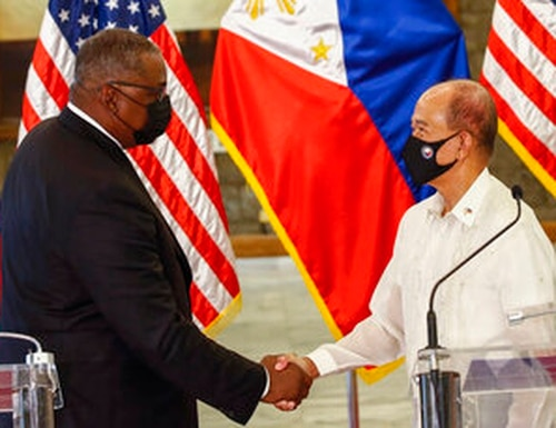 United States Defense Secretary Lloyd Austin, left, and Philippines Defense Secretary Delfin Lorenzana shake hands after a bilateral meeting at Camp Aguinaldo military camp in Quezon City, Metro Manila, Philippines Friday, July 30, 2021. (Rolex dela Pena/Pool Photo via AP)