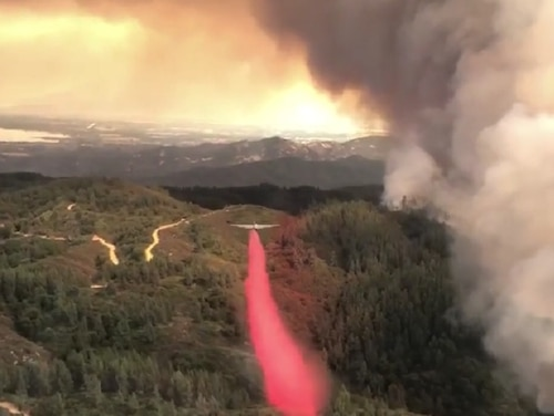 Airmen operating a U.S. Forest Service HC-130H tanker drop fire retardant on the River Fire near Mendocino, California, July 28. (Screen grab from video by Capt. Aaron Moshier/Air Force)