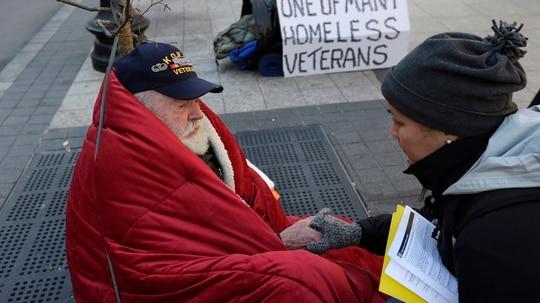 A homeless Korean War veteran speaks with a Boston Health Care outreach coordinator on a sidewalk in that city in November 2013. (Steven Senne/AP)
