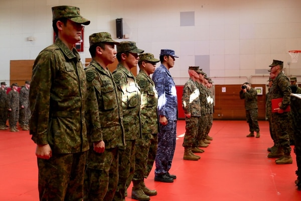 Members of Japan's new Amphibious Rapid Deployment Brigade and U.S. forces are recognized at the end of the Yama Sakura 75 exercise. There are 2,100 Japanese forces in the new brigade, with 3,000 expected by March. (Tara Copp/Military Times)