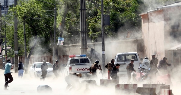 Security forces run from the site of a suicide attack after the second bombing in Kabul, Afghanistan, Monday, April 30, 2018. A coordinated double suicide bombing hit central Kabul. (Massoud Hossaini/AP)