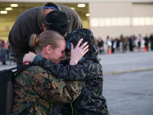 A Marine embraces her son and husband aboard Marine Corps Air Station Beaufort Jan. 12. The Marine is returning from a six-month deployment in the Western Pacific as part of the Unit Deployment Program. Marines deployed to Japan and Guam for six months to improve unit operability. The Marine is with Marine Fighter Attack Squadron 312, Marine Aircraft Group 31.