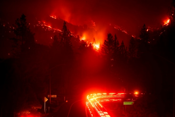 Fire trucks pass the Delta Fire burning in the Shasta-Trinity National Forest, Calif., on Wednesday. Parked trucks lined more than two miles of Interstate 5 as both directions remained closed to traffic. (Noah Berger/AP)