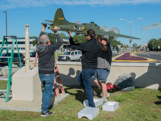 Gino Galvez, left, an Atlantic-Models scale model manufacturer, Stephen Ove, center,, the 6th Air Refueling Wing historian and Roger Jarman, the Atlantic-Models vice president, lift a scale model of the Memphis Belle, a B-17 Flying Fortress, onto a display stand Jan. 8 at MacDill Air Force Base, Fla. (Airman 1st Class Shannon Bowman/Air Force)