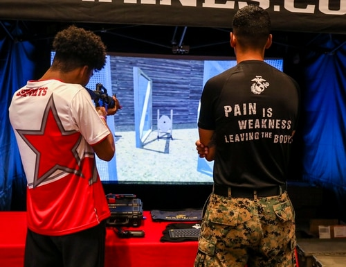 U.S. Marine Corps Sgt. Peter Lopez, a recruiter with the 8th Marine Corps District, oversees a spectator operating the marksmanship trainer during Ultimatum II, a Smash Ultimate Tournament hosted by Esports Stadium Arlington, in Arlington, Texas, December 27, 2019. (Cpl. Desmond Andrews/Marine Corps)