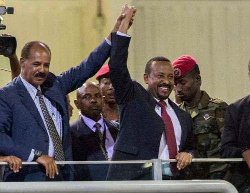On July 15, 2018, Eritrean President Isaias Afwerki, second left, and Ethiopia's Prime Minister Abiy Ahmed, center, hold hands as they wave at the crowds in Addis Ababa, Ethiopia. Once rivals, the leaders of Ethiopia and Eritrea celebrated the end of a long state of war. The 2019 Nobel Peace Prize was given to Ethiopian Prime Minister Abiy Ahmed on Friday. (Mulugeta Ayene/AP)