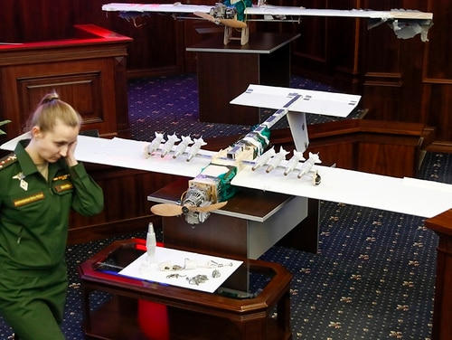 A Russian officer walks next to drones that attacked a Russian airbase in Syria and were captured and displayed at a briefing in the Russian Defense Ministry in Moscow in early January. (Pavel Golovkin/AP)