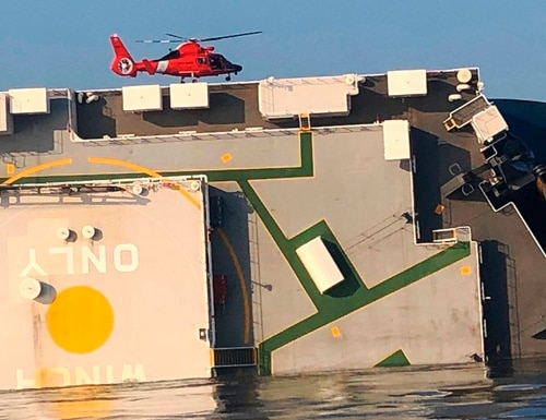A USCG helicopter hovers over an overturned cargo ship in St. Simons Sound, Ga., on Monday. (Coast Guard via AP)