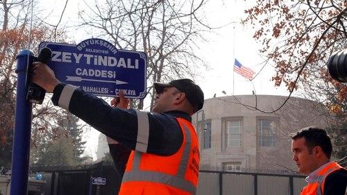 An Ankara municipality worker fixes the new street sign,