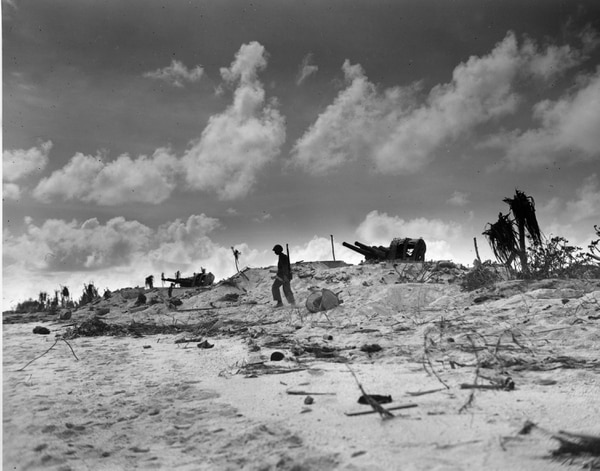 With two captured Japanese naval guns as a backdrop, a lone U.S. Marine is patroling the beach at Tarawa atoll, December 6, 1943, during the invasion of Gilbert Islands in World War II. (AP Photo)