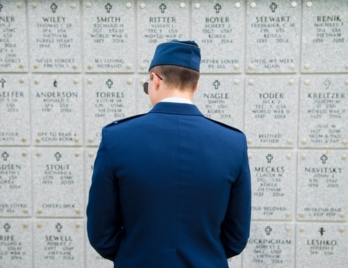 1st Lt. Matt Brown, a 62nd Fighter Squadron pilot, looks at the name of deceased service members at the Indiantown Gap National Cemetery in Annville, Penn., Aug. 4, 2017. Before attending 2nd Lt. Charles E. Carlson's funeral, several Airmen reflected upon the thousands of gravesites. (Staff Sgt. Jensen Stidham/Air Force)