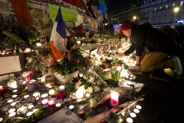 A man lights a candle at a makeshift memorial in tribute to the victims of Paris' attacks' on November 15, 2015 at the place de la Republique in Paris. Islamic State jihadists claimed a series of coordinated attacks by gunmen and suicide bombers in Paris on November 13 that killed at least 129 people in scenes of carnage at a concert hall, restaurants and the national stadium. AFP PHOTO / JOEL SAGET (Photo credit should read JOEL SAGET/AFP/Getty Images)