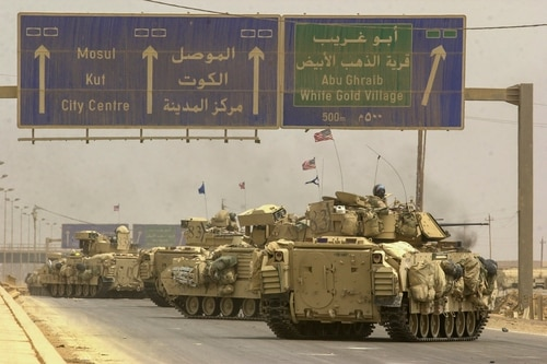 Vehicles from the U.S. Army's 3rd Infantry Division, 3rd Brigade rumble along an access road to highway 10 enroute to the Northwestern side of the city, to complete the encirclement of Baghdad. The 3rd Squadron, 7th Cavalry Regiment has had some fierce fighting on highway 10 over the last two days, killing close to 1000 Iraqi soldiers in vehicles ranging from tanks to buses loaded with explosives. The Cavalry's job was to secure the highway and allow safe pasage of the rest of the 3rd Brigade. (Warren Zinn/Army Times)