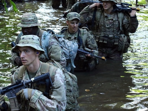 Soldiers assigned to Army Africa wade through water during jungle warfare training on the continent. (Army)