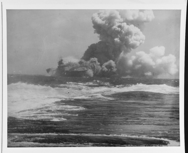The aircraft carrier Wasp, afire and sinking south of San Cristobal Island after being torpedoed by a Japanese submarine, on 15 September 1942, as seen from the cruiser San Francisco. (National Archives)