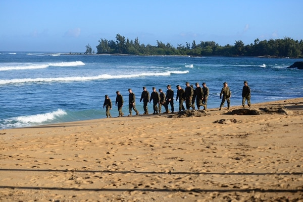 A group of Marines walk the beach outside the Haleiwa Incident Command Post in Haleiwa, Hawaii, during search efforts for 12 missing Marines, Jan. 18, 2016. The Marines are leading a multi-agency shoreside search effort for 12 Marines who went missing after being involved in a helicopter crash off the North Shore of Oahu. (U.S. Coast Guard photo by Petty Officer 1st Class Levi Read/Released)