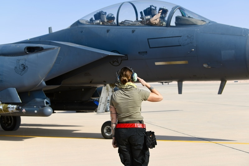Air Force Senior Airman Emily Kline, a crew chief with the 378th Expeditionary Maintenance Squadron, salutes the F-15E Strike Eagle's pilot prior to a sortie at Prince Sultan Air Base, Kingdom of Saudi Arabia, Jan. 8, 2020. The 494th Expeditionary Fighter Squadron completed the first combat sortie from PSAB since 2003. (Tech. Sgt. Michael Charles/Air Force)