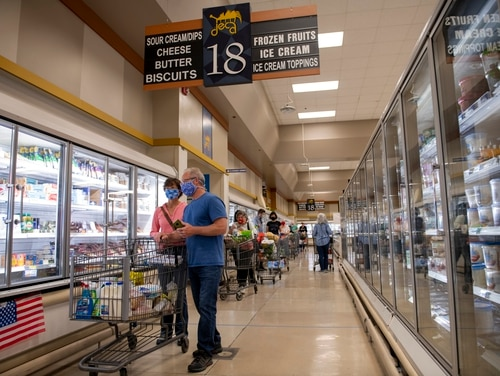 Socially-distanced, masked shoppers wait to pay for their groceries April 16, 2020, inside the commissary at Travis Air Force Base, Calif. (Tech. Sgt. James Hodgman/Air Force)