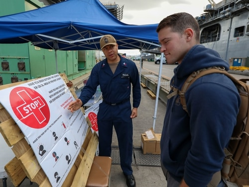 On March 25, Hospital Corpsmen 1st Class Jonathan Ivey, left, screens Ensign Mackenzie Jones for signs of the coronavirus before allowing him to board the amphibious assault ship USS Makin Island (LHD 8). (US Navy photo by Mass Communication Specialist 2nd Class Jeremy Laramore)